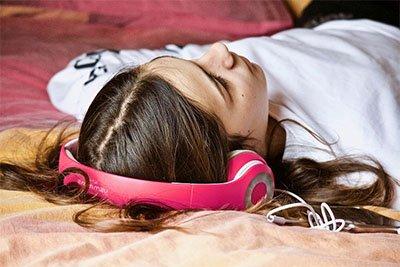 Wanita menggunakan headphone terbaik untuk meredam suara bising dan bersantai