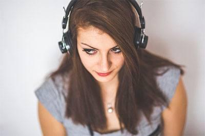 Wanita menggunakan headphone terbaik bertipe in ear yang nyaman