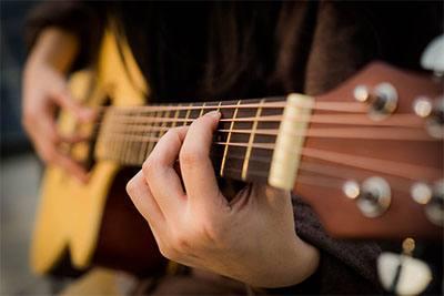 Memainkan gitar akustik